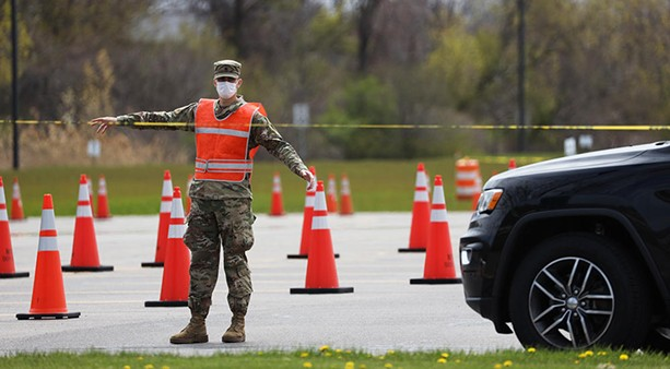 A worker at the state-run coronavirus testing site at Monroe Community College's Brighton campus directs a driver through the parking lot. - PHOTO BY MAX SCHULTE / WXXI NEWS