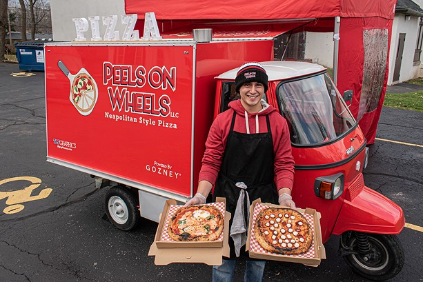 Luis Perez with a couple of Neapolitan pizza pies outside his Peels on Wheels Piaggio Ape - PHOTO BY JACOB WALSH