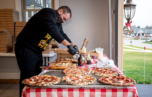 Jim Zobel of Doughboyz serves up pizza at a pop-up location in Greece. - PHOTO BY JACOB WALSH