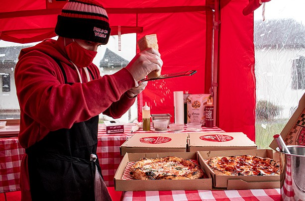Luis Perez makes some pizzas in an enclosure adjacent to his converted Piaggio Ape P601 - PHOTO BY JACOB WALSH