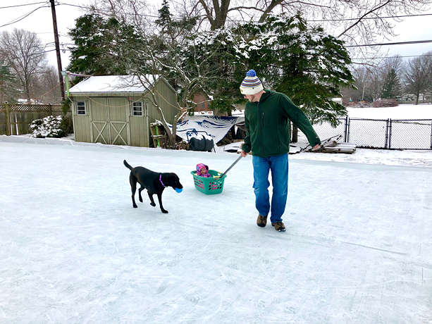 "Joseph Climek slides his daughter around on ""Mos Iceley,"" his backyard rink in Webster. - PHOTO COURTESY OF JOSEPH CLIMEK AND MELODY KING"