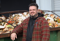 Robert Putney, Impact Earth founder and CEO, in front of a Dumpster filled with food waste. - PHOTO BY MAX SCHULTE