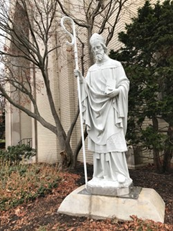 The statue of St. Boniface, outside of St. Boniface Catholic Church in the South Wedge, with its new staff dedicated to Margaret Nordbye, who was remembered as a shepherd of the neighborhood. - PHOTO BY DAVID ANDREATTA