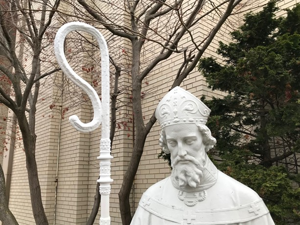 The statue of St. Boniface outside the namesake Catholic church in the South Wedge has a new staff dedicated to Margaret Nordbye, who was called 'a shepherd of the neighborhood.' - PHOTO BY DAVID ANDREATTA