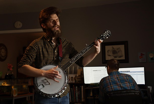 Philip Detrick plays the banjo as his brother works from home. Detrick moved into his brother's Webster home in September and hopes to get his own apartment soon. - PHOTO BY MAX SCHULTE