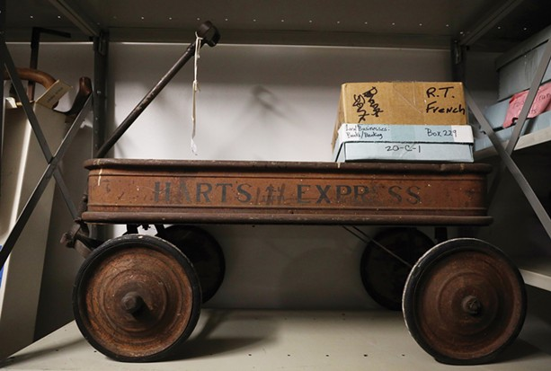 A vintage steel wagon from Hart's grocery store circa 1900 sits on a shelf at the Rochester Historical Society's new home on University Avenue. - PHOTO BY MAX SCHULTE