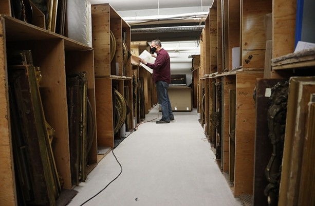 The Rochester Historical Society archivist Bill Keeler sifts through old painting and drawings of locals collected over the years. The new location doesn't have wall space to hang all the works in wood stacks. - PHOTO BY MAX SCHULTE