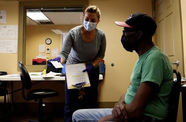 VA Finger Lakes Healthcare System nurse, Lisa Lehning, shows C.L. Scribling the CDC vaccination card he'll receive after his shot of the Johnson & Johnson COVID-19 vaccine. - PHOTO BY MAX SCHULTE / WXXI NEWS