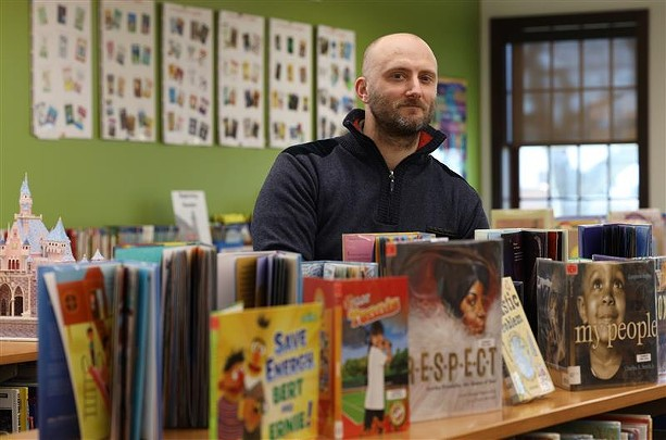 Irondequoit Public Library Director Greg Benoit stands among stacks of children books. The library is eliminating late fee charges on items geared toward children and young adults. - PHOTO BY MAX SCHULTE