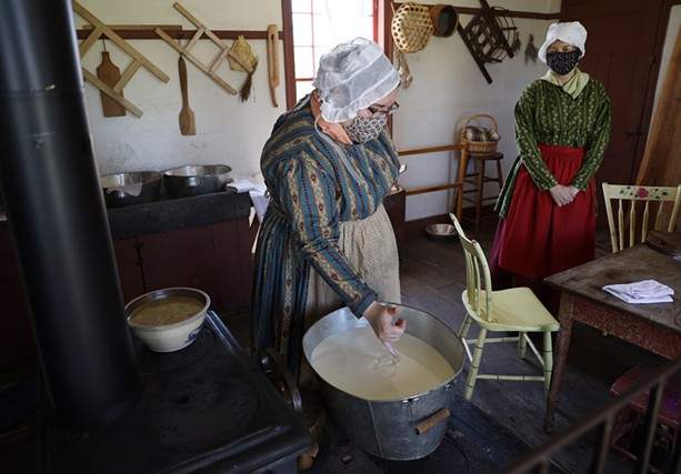 Historic interpreters engaged in an old process of cheese-making, in an 1830s farmhouse kitchen at Genesee Country Village & Museum. - PHOTO BY MAX SCHULTE