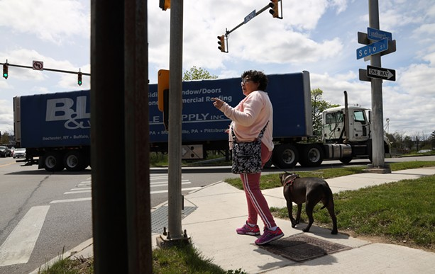 """Nancy Hernandez Maciuska, a member of the Lewis Street Committee walks her dog, Hope, along Scio Street as trucks pull off the Inner Loop exit onto Lyndhurst Street. Of city talk to fill in the Inner Loop, she says, """"We want to be heard."""" - PHOTO BY MAX SCHULTE"""