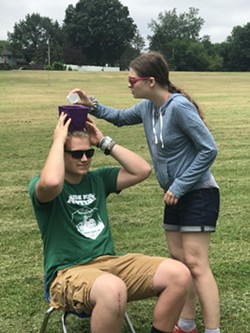 A camper pours water into a bucket on top of a counselor's head in a camp activity in the summer of 2019. - PHOTO BY EMMA BENZ
