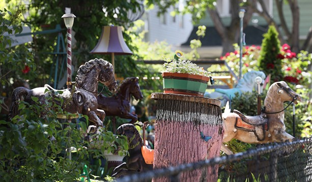 Most of the more than 120 horses in the Rodriguezes' yard at the corner of North and St. Jacob streets have been dismantled from their spring-based rockers and placed between flowers and trees. - PHOTO BY MAX SCHULTE