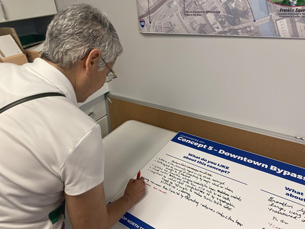 Maria Furgiuele, executive director of the Community Design Center of Rochester, makes notes under an Inner Loop fill-in concept. - PHOTO BY JAMES BROWN