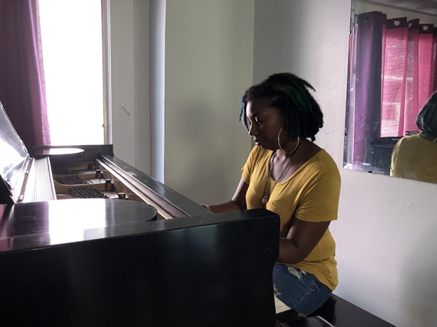Avis Reese plays the grand piano gifted to her by a stranger. A friend will store the piano until Reese decides where she'll make her new home. - PHOTO BY BETH ADAMS, WXXI NEWS