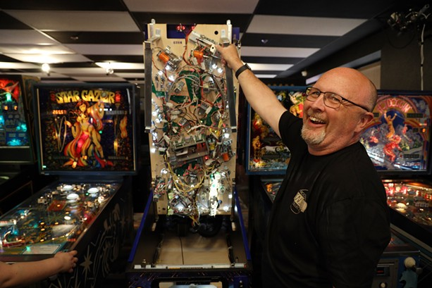 Bruce Nightingale displays the guts of a modern pinball machine. More than half the machines at Rochester Pinball Collective are from his personal collection. - PHOTO BY MAX SCHULTE
