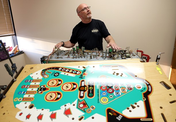"""Bruce Nightingale explains the intricacies of a """"playfield swap"""" being done on a 1977 Eight Ball game, in which all the circuitry is transferred from an old playfield to a new one. - PHOTO BY MAX SCHULTE"""