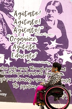 Luticha Doucette poses in front of a Susan B. Anthony mural in Rochester. - PHOTO BY ERICA JAE