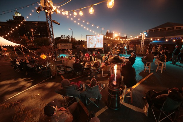 Rochester Fringe festivalgoers watch a movie outdoors at One Fringe Place. - PHOTO PROVIDED
