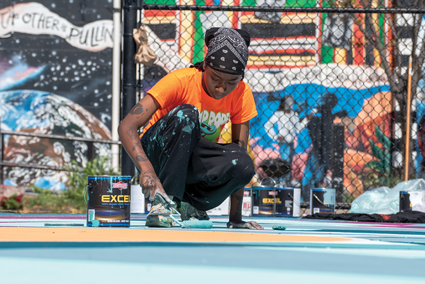 Paris Cockrell, part of the 2021 Peculiar Asphalt team, paints this year's final basketball court at the Roxie Ann Sinkler R-Center. - PHOTO BY RYAN WILLIAMSON