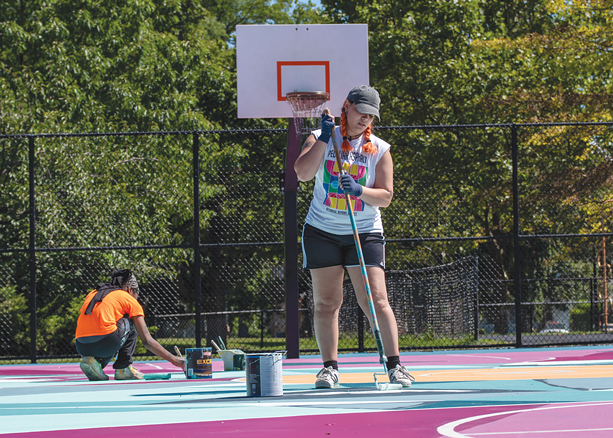 Paris Cockrell and Francheska Diaz (foreground) work to finish painting the basketball court at Roxie Ann Sinkler R-Center on Sept. 2021. - PHOTO BY RYAN WILLIAMSON