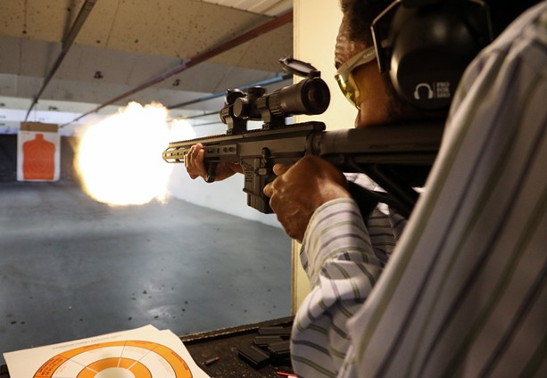 Quinn Lawrence, a self-defense instructor with the Rochester African American Firearms Association, fires away during target practice at The Firing Pin in Bergen. - PHOTO BY MAX SCHULTE