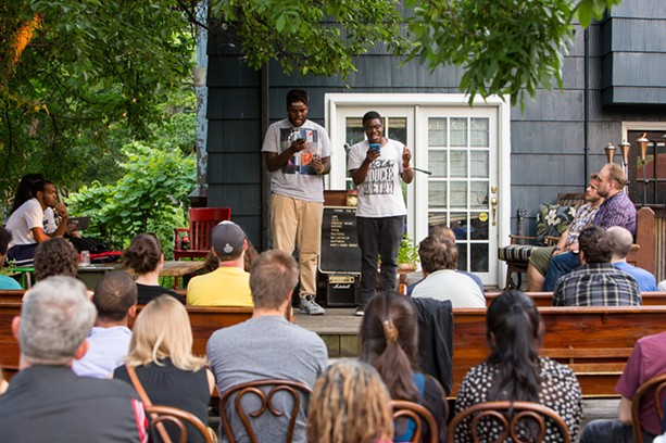 Two high school students perform their works before an audience at the July 11 Poetry & Pie Night. The two young writers opened for the established poets Scott Woods and Chen Chen. - PHOTO BY JOHN SCHLIA