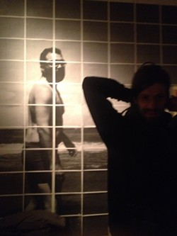 Musician and artist Joel Dow in front of John Lake's photo installation at Axom. - PHOTO BY REBECCA RAFFERTY