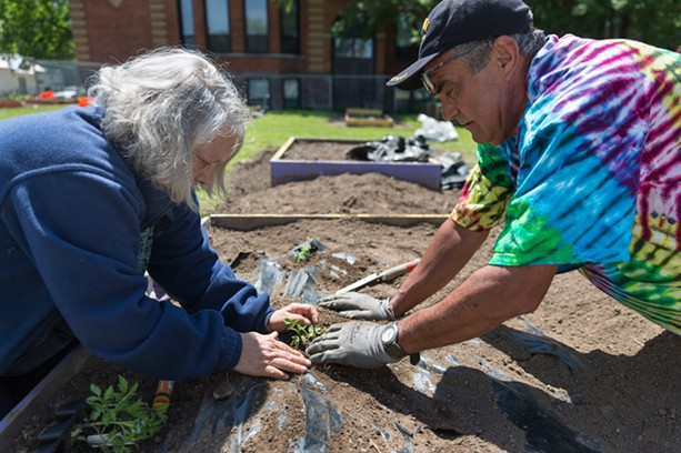 Members of the Marketview Heights Collective Action Project grow food, flowers, and community. - Judy Douglas and Martin Pedraza tend one of the neighborhood's gardens. - PHOTO BY AUDREY HORN