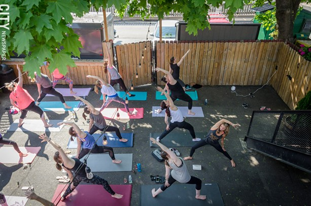 A yoga class during a session in the back of The Daily Refresher. - PHOTO BY MARK CHAMBERLIN