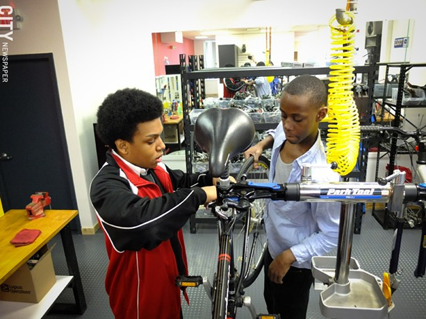 David Gayle,16, and Shandan Jones,17, both of Vertus High School, change a wheel at Dream Bikes on University Avenue. - PHOTO BY KEVIN FULLER