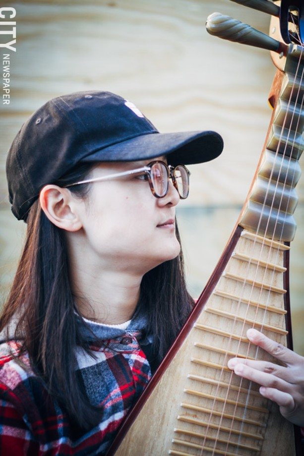 """Leah Ou, a Chinese Pipa player, said a lot of market goers stop by to ask her about her instrument, which is a four-stringed, pear-shaped string instrument from China. - """"I like it. People are friendly."""" - PHOTO BY KEVIN FULLER"""