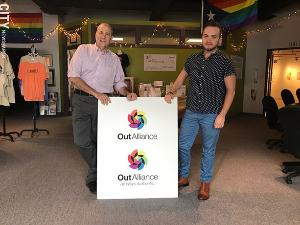 Gay Alliance Executive Director Scott Fearing (left) and Education Coordinator Rowan Collins, with the organization's new logo and signage. - PHOTO BY RYAN WILLIAMSON