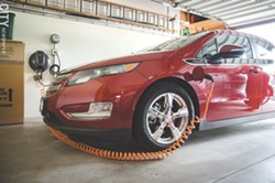 The Rochester Electric Vehicle Accelerator wants to increase the number electric vehicles and plug-in hybrids, such as this Chevrolet Volt hooked up to an at-home charger, that are on Rochester's roads. - FILE PHOTO