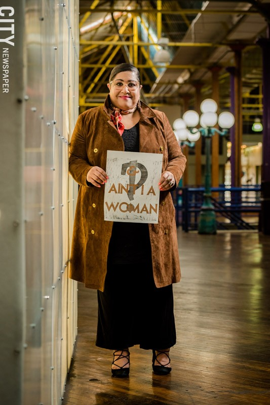 """Rachel Y. DeGuzman holds a work by Rochester artist Amanda Chestnut, who created the piece for the recent 21st Century Arts event """"And, Ain't I a Woman: A Long Table Conversation and Installation."""" - PHOTO BY JOSH SAUNDERS"""
