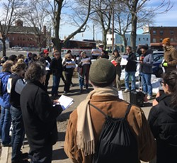Justin Delinois, an organizer with UR DREAMers, addresses a crowd of about 40 people outside of the Rochester Greyhound and New York Trailways station. - PHOTO BY JAKE CLAPP