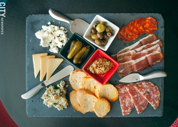 Bliss's charcuterie board is loaded with three types of meat, three types of cheese, bread, olives, gherkins, and mustard. - PHOTO BY RENÉE HEININGER