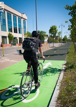A bicyclist rides on the new cycle tracks the city built on Union Street, as part of the Inner Loop fill-in project. - PHOTO BY RENÉE HEININGER