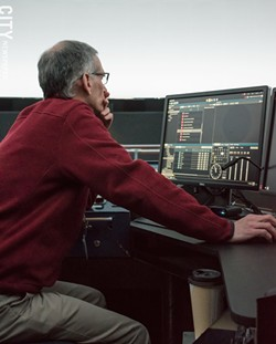 Planetarium director Steve Fentress tweaks details in Star Theater's control booth. - PHOTO BY JACOB WALSH