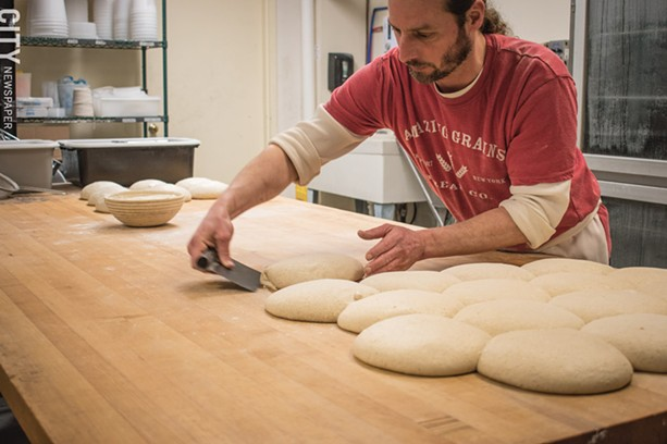 An Amazing Grains worker prepares bread dough. - PHOTO BY JACOB WALSH