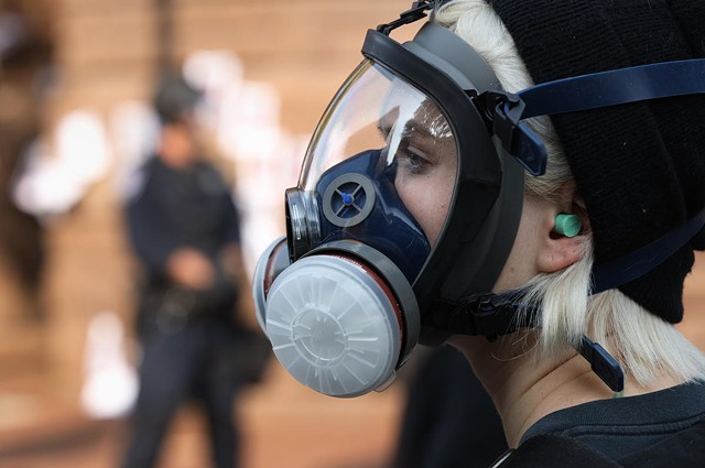 A protester wears a gas mask during a standoff with Rochester police outside City Hall on Sept. 16.