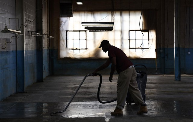 Eddie Chapple cleans and polishes a floor at an industrial park in Rochester's west side. He landed his job with CleanCraft through the open hiring process.