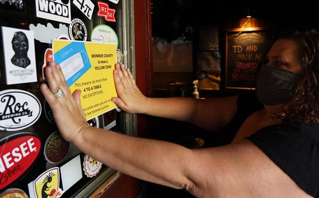 Kelly Bush, owner of the Marshall Street Bar and Grill, posts a notice at her restaurant on Tuesday, Nov. 10, 2020.