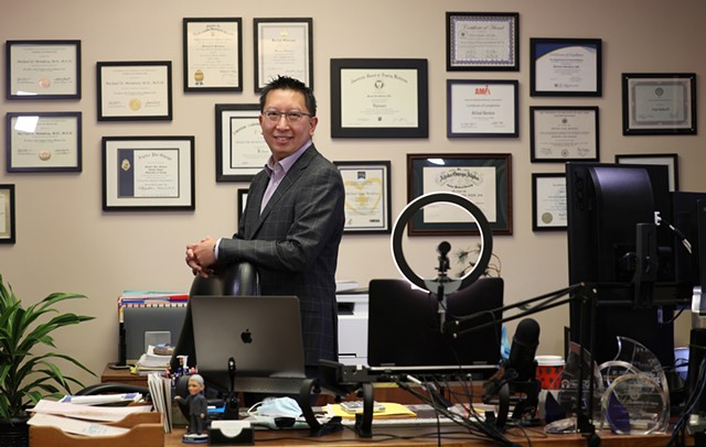 Monroe County Public Health Commissioner Dr. Michael Mendoza in his office at the county Health Department. His wall of citations has become a familiar backdrop for his frequent video news briefings during the pandemic.