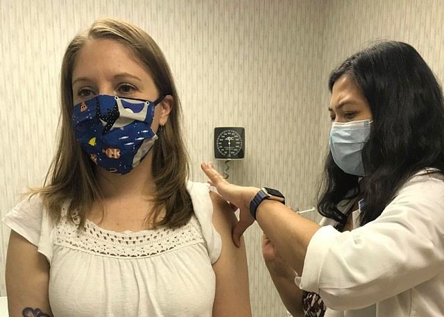 Becky Timmons gets her first dose of a vaccine trial for the novel coronavirus at Rochester General Hospital.
