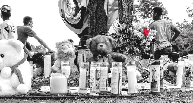 Memorials spread out across the parking lot in front of the Boys and Girls Club on Genesee Street, where three people were murdered and four others injured last week.