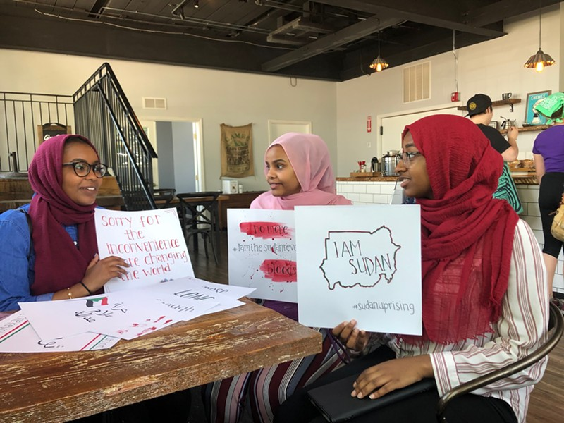Rana Sulieman (left), Hiba Ahmed, and Olaa Mohamed hold signs they've made for Saturday's protest. - PHOTO BY EFUA AGYARE-KUMI