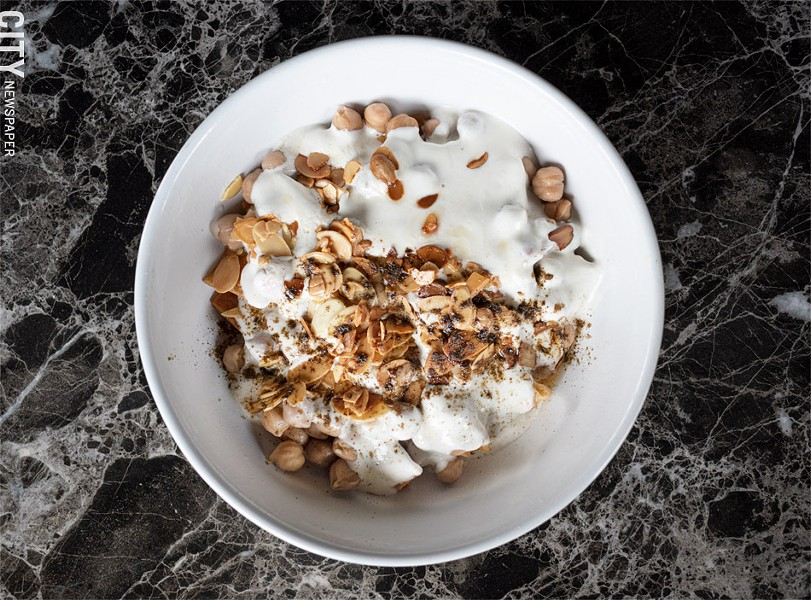 The original fetteh bowl (a comfort food staple) includes chickpeas and yogurt sauce, and is garnished with toasted almonds and aromatic spices. - PHOTO BY JACOB WALSH