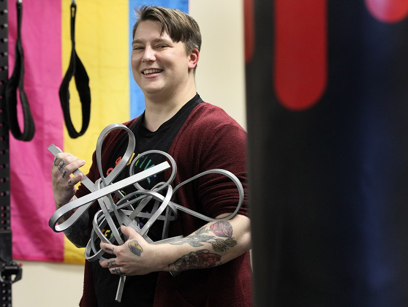 """Lore McSpadden, one of the founders of Positive Force Movement, stands with a sculpture they made by bending steel with nothing but the strength and leverage of their own body. """"I can't do it again for a few more weeks, though,"""" McSpadden says. """"I had top surgery last month."""" - PHOTO BY MAX SCHULTE"""