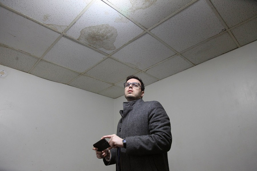 Mike Furlano, an attorney with the Legal Aid Society of Rochester, photographs water stains and damaged ceiling tiles in one room of Linda Barger's apartment. - PHOTO BY MAX SCHULTE